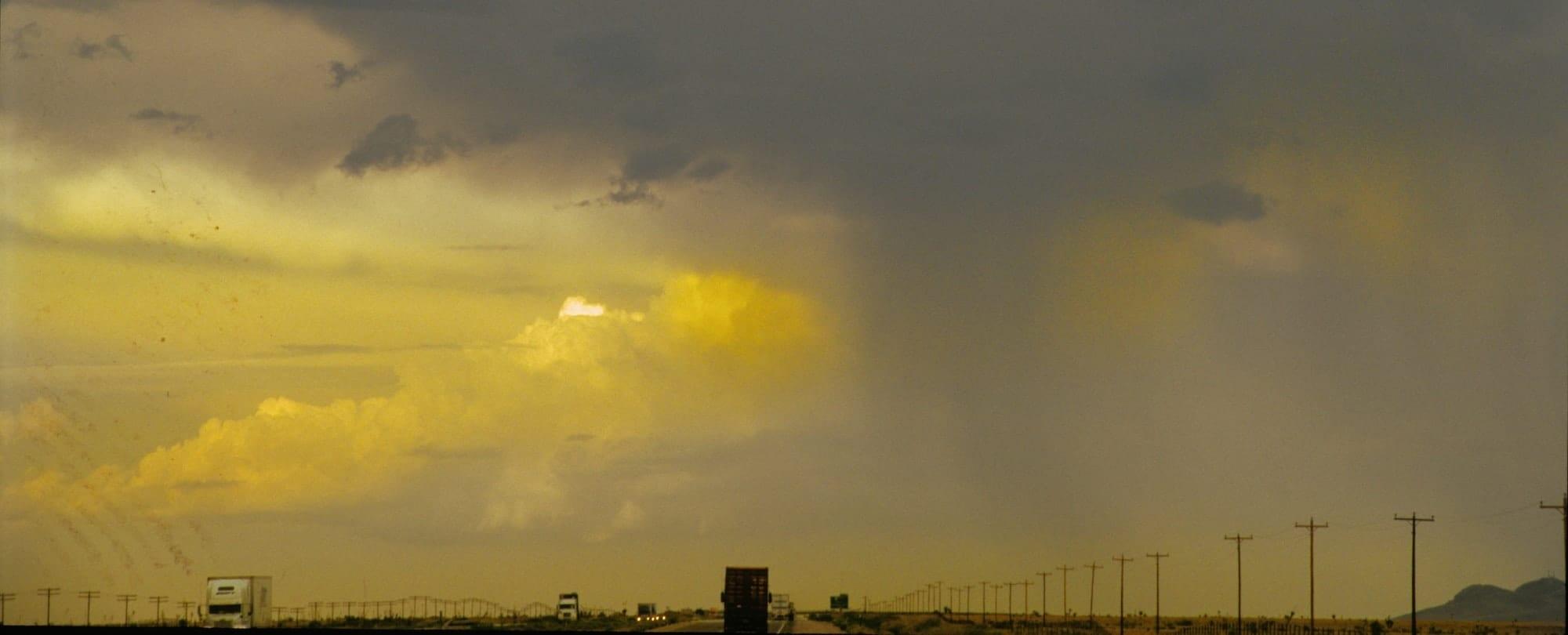 Immagine casuale che richiama alla serendipità: nell'immagine si vede una strada trafficata, sullo sfondo vi è un temporale