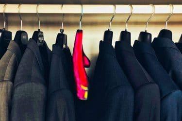 Un armadio con tutti gli appendini neri e un differente poiché rosso acceso