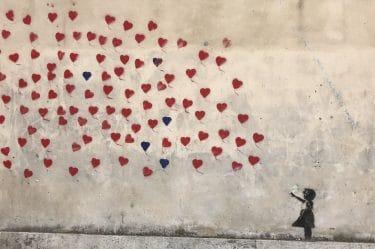 Una bambina proiettata sul futuro che guarda dei cuori disegnati su un muro