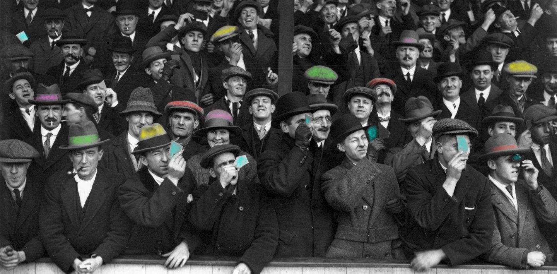 una foto di una folla in bianco e nero se non per i colori dei cappelli accessi che creano smarrimento