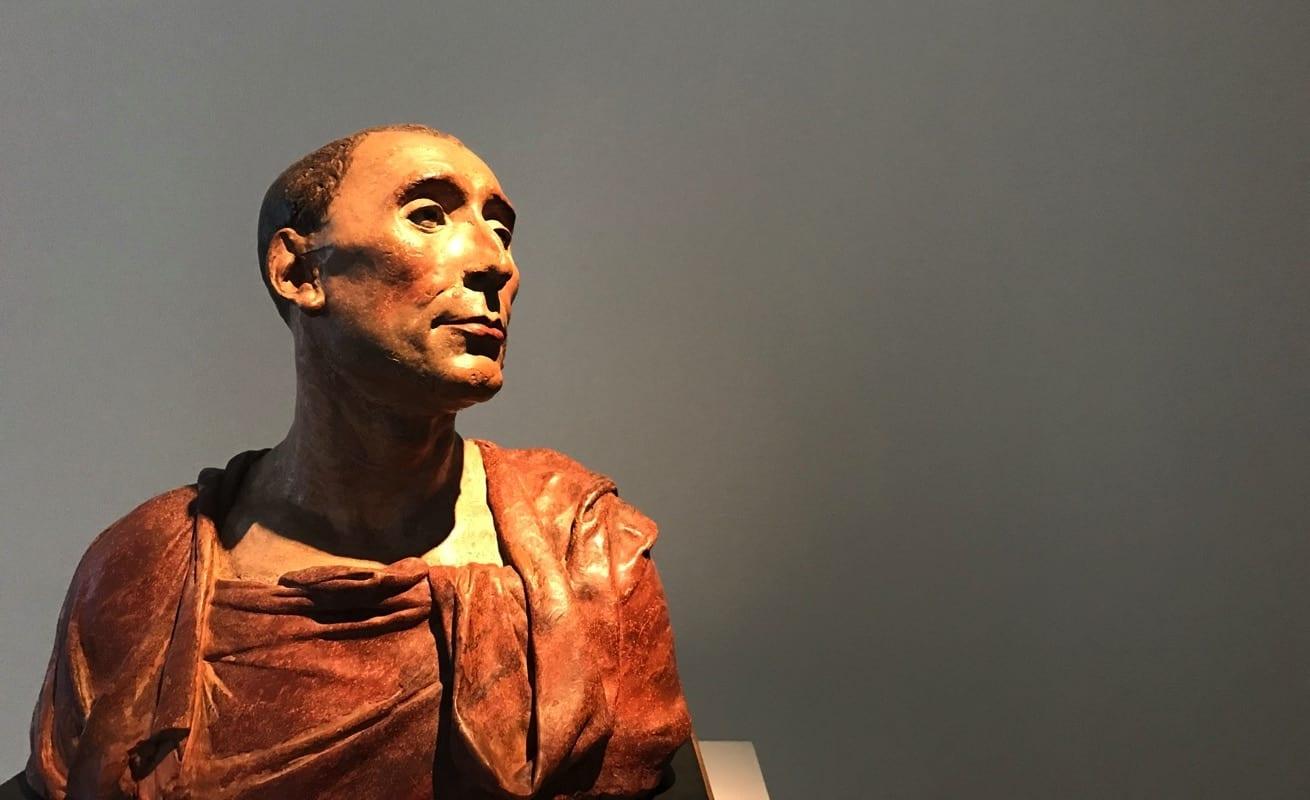 Statua di un pensatore romano in tunica che si pone domande esistenziali sull'identità-