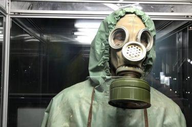 immagine di una persona con tuta e maschera che sembra andare in un impianto nucleare.