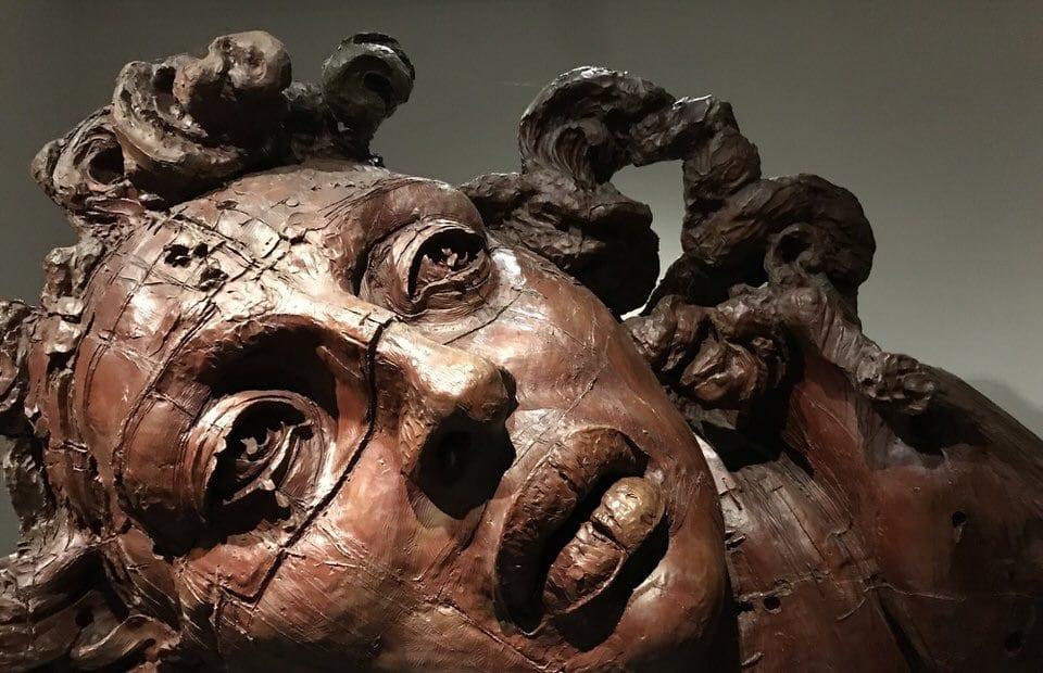 L'immagine mostra il viso di una statua. Dall'espressione sembra abbia alcuni segreti da nacondere