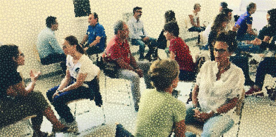 L'immagine mostra un gruppo di persone impegnate in colloqui uno ad uno. L'immagine richiama all'empatia