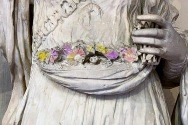 statua che tiene un cesto di fiori colorati